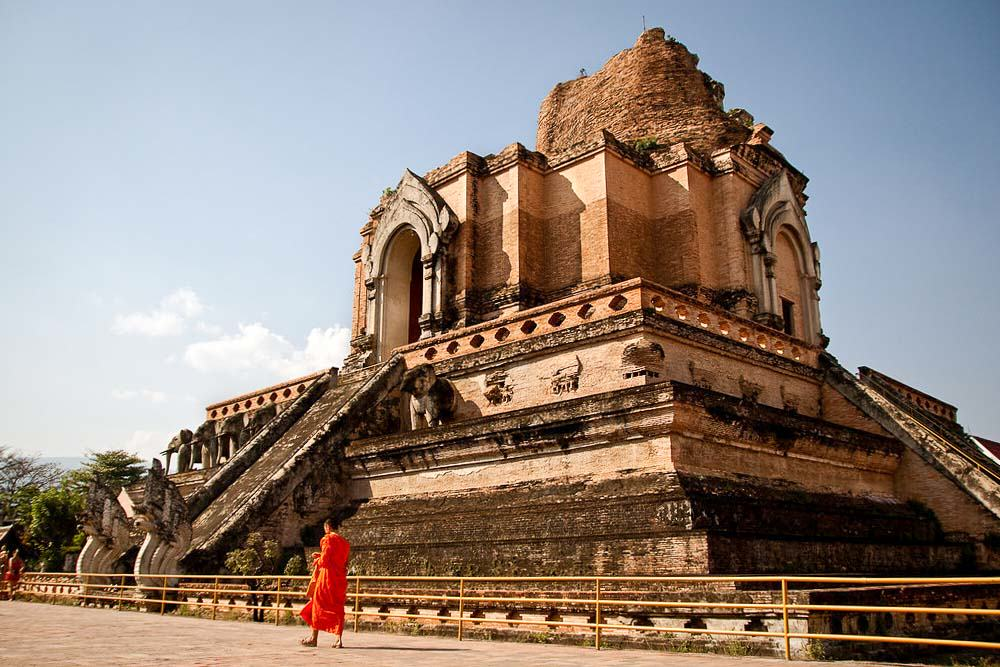 Monk walking past the grand Wat Chedi Luang temple in Chiang Mai